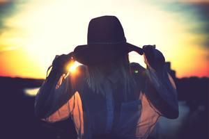 une femme se protège du soleil par un grand chapeau