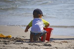 un petit enfant joue dans le sable protégé du soleil