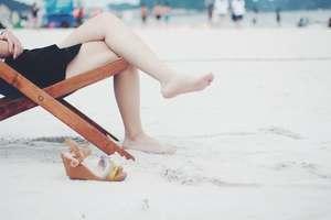 Femme pieds nus dans le sable après avoir posé ses sandales compensées