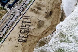le mot résister est écrit sur la plage comem pour dire de ne pas prendre de bonnes résolutions