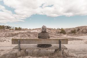 Femme seule sur un banc qui vite le syndrome du nid vide