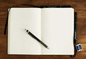 un cahier avec des pages blanches et un stylo pour accueillir les mots