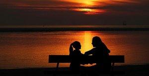 une femme et une petite fille échangent des mots sur un banc devant un coucher de soleil