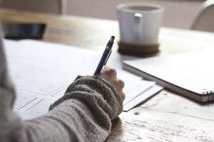 une main écrit des mots dans un journal intime