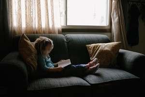 une petite fille lit des mots sur un canapé