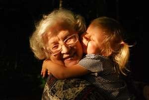 une petite fille embrasse sa grand-mère