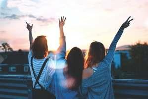 trois femmes de dos qui lèvent les bras