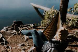 femme seule et libre assise dehors sur un hamac